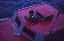 Photograph of a man looking out of the cabin of his boat in North West River, Newfoundland and La...