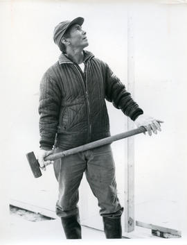 Photograph of a man holding a sledgehammer in Fort Chimo, Quebec