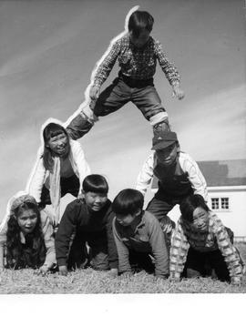 Photograph of children making a human pyramid in Cape Dorset, Northwest Territories