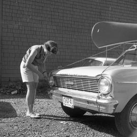 Photograph of an unidentified woman tying a canoe to the roof of a car