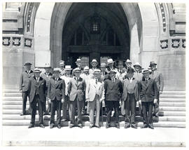 Photograph of 20 unidentified people on steps of large building related to health meetings