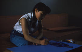 Photograph of a girl with braids sitting on a couch and drawing