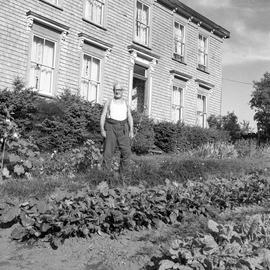 Photograph of Mr. Farrant standing in a garden in front of a house