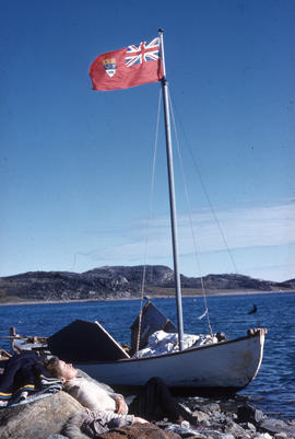 Photograph of a small boat that is flying a Canadian flag