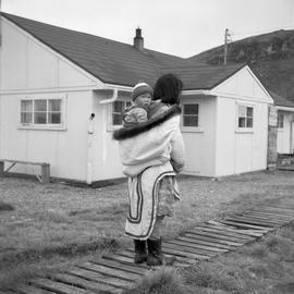 Photograph of and unidentified woman carrying a baby in Sugluk, Quebec