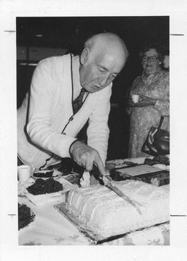Photograph of Jim Campbell cutting a cake