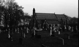 Photograph of a graveyard and church