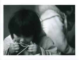 Photograph of an unidentified girl making something with string