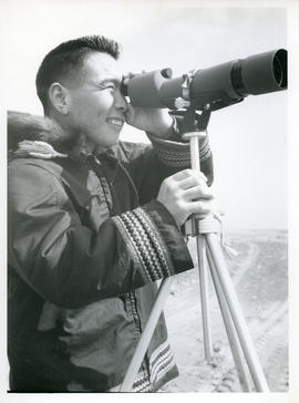 Photograph of a man looking through a telescope