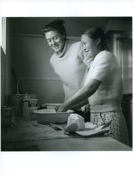 Photograph of Barbara Hinds and an unidentified girl making something in a kitchen