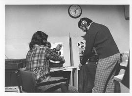 Photograph of two unidentified people with audiovisual equipment