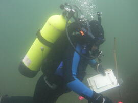 Photograph of diver with clipboard underwater