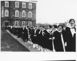 Photograph of graduating students lined up next to yr Science Building
