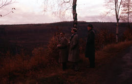 Photograph of three unidentified men near old farms (alte hofe)