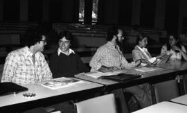 Photograph of five unidentified people sitting at desks