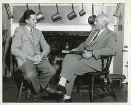 Photograph of Thomas Head Raddall holding a book and speaking with CBC interviewer Lloyd MacInnis...