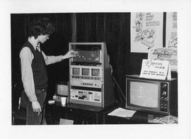 Photograph of an unidentified person looking at a display by T.V. services