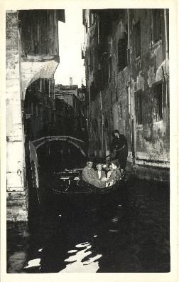 Photograph of Thomas Head and Edith Raddall riding a gondola in Venice, Italy printed on a postcard