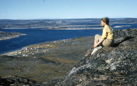 Photograph of Barbara Hinds sitting on a mountain overlooking Cape Dorset, Northwest Territories