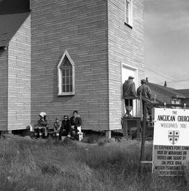 Photograph of several people waiting outside of the St. Stephen's Anglican church in Fort Chimo, ...