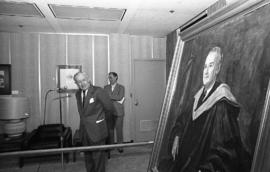 Photograph of an unidentified person looking at a painting of Chester Stewart