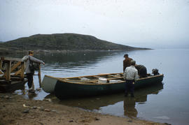 Photograph of four people with two canoes in Frobisher Bay