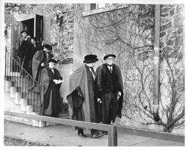 Photograph of unidentified people in robes walking downstairs outside