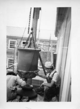 Photograph of men lifting a stone stulpture with chains