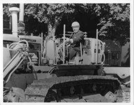Photograph and photographic negative of President Henry Hicks on a bulldozer