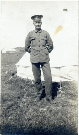 Portrait of T.H. Raddall, Sr. in uniform standing in front of a tent at Valcartier Camp, Quebec