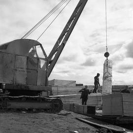 Photograph of construction material being lifted with a crane
