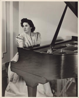 Publicity photograph of Ellen Ballon playing a piano