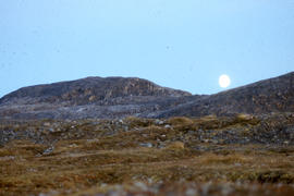Photograph of the moon rising over a hill in Cape Dorset, Northwest Territories