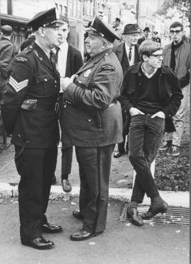 Photograph of two police officers conversing in Halifax's Grand Parade while, off-camera, marcher...