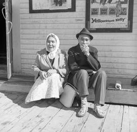 Photograph of a man and a woman sitting in front of a building in Dawson City, Yukon