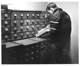 Photograph of a student using the card catalogue in the Macdonald library
