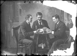 Photograph of 3 individuals playing cards