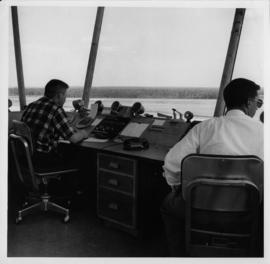 Photograph of two unidentified people sitting at an airport control tower