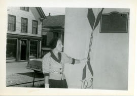 Photograph of Edith Raddall drawing a Nova Scotian flag aside to unveil the Marshall Saunders mem...