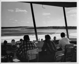 Photograph of three unidentified people sitting at an airport control tower