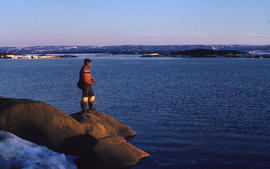 Photograph of an unidentified man fishing on the shore of Frobisher Bay