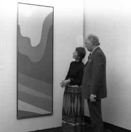 Photograph of two unidentified people with a painting