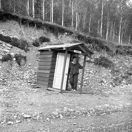 Photograph of Barbara Hinds standing in front of an outhouse in the Yukon