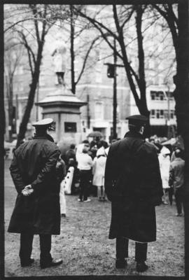 Photograph of two police officers standing behind a group of protesters listening to speakers at ...
