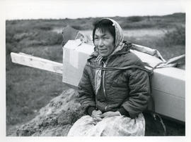 Photograph of a woman carrying pieces of a packing case with a harness in Fort Chimo, Quebec