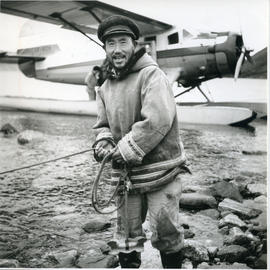 Photograph of Ningiok standing by an airplane at Wakeham Bay, Quebec