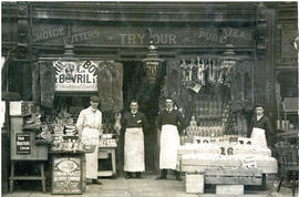 Photograph of four men, including T.H. Raddall, Sr., wearing aprons outside a grocery store