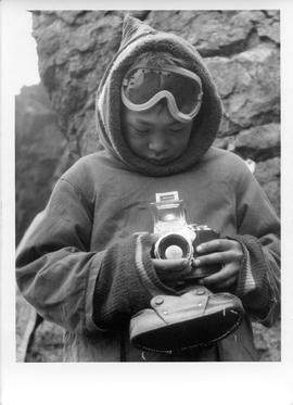 Photograph of an unidentified boy holding a camera