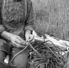 Photograph of an unidentified man working with a rope