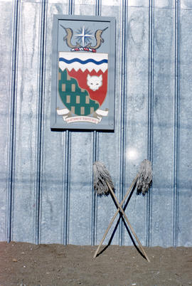 Photograph of the Northwest Territories crest and two mops on the side of a building in Frobisher...